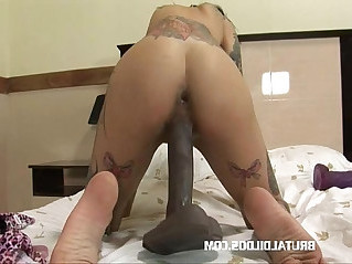 Tattood babe filling her wet pussy with brutal dildo